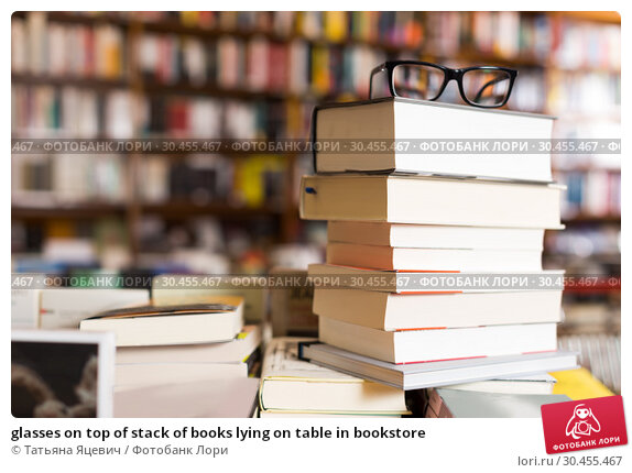 glasses on top of stack of books lying on table in bookstore. Стоковое фото, фотограф Татьяна Яцевич / Фотобанк Лори