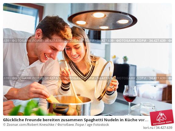 Glückliche Freunde bereiten zusammen Spaghetti Nudeln in Küche vor... Стоковое фото, фотограф Zoonar.com/Robert Kneschke / age Fotostock / Фотобанк Лори