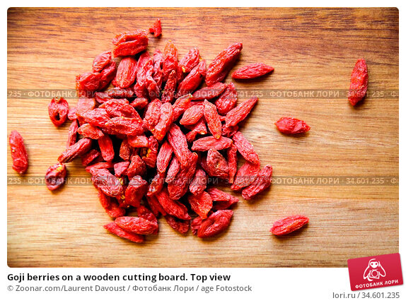 Goji berries on a wooden cutting board. Top view. Стоковое фото, фотограф Zoonar.com/Laurent Davoust / age Fotostock / Фотобанк Лори