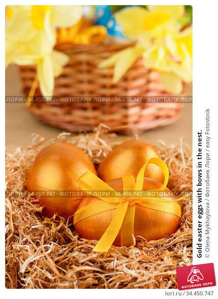 Gold easter eggs with bows in the nest. Стоковое фото, фотограф Olena Mykhaylova / easy Fotostock / Фотобанк Лори