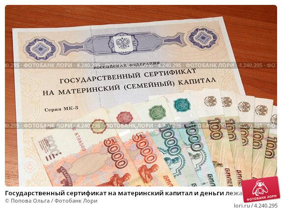 Купить «Государственный сертификат на материнский капитал и деньги лежат на столе», фото № 4240295, снято 29 января 2013 г. (c) Попова Ольга / Фотобанк Лори