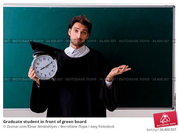 Graduate student in front of green board. Стоковое фото, фотограф Zoonar.com/Elnur Amikishiyev / easy Fotostock / Фотобанк Лори