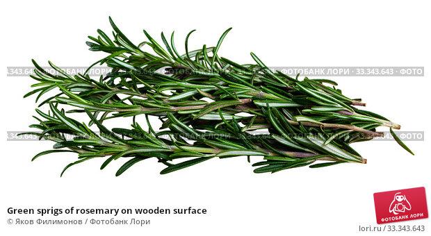 Купить «Green sprigs of rosemary on wooden surface», фото № 33343643, снято 8 июля 2020 г. (c) Яков Филимонов / Фотобанк Лори