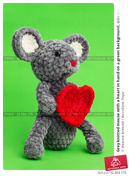 Grey knitted mouse with a heart in hand on a green background, side view. Стоковое фото, фотограф Иванов Алексей / Фотобанк Лори