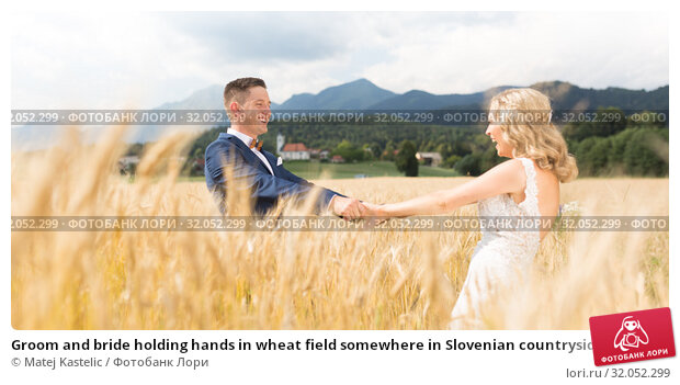 Groom and bride holding hands in wheat field somewhere in Slovenian countryside. Стоковое фото, фотограф Matej Kastelic / Фотобанк Лори
