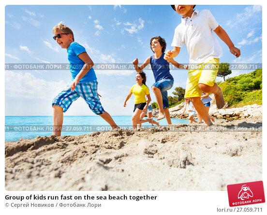 Купить «Group of kids run fast on the sea beach together», фото № 27059711, снято 20 июля 2017 г. (c) Сергей Новиков / Фотобанк Лори