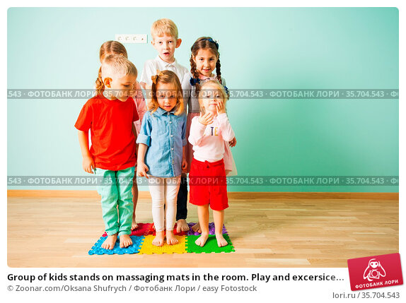Group of kids stands on massaging mats in the room. Play and excersice... Стоковое фото, фотограф Zoonar.com/Oksana Shufrych / easy Fotostock / Фотобанк Лори