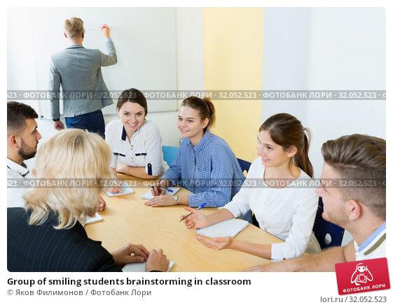 Group of smiling students brainstorming in classroom. Стоковое фото, фотограф Яков Филимонов / Фотобанк Лори