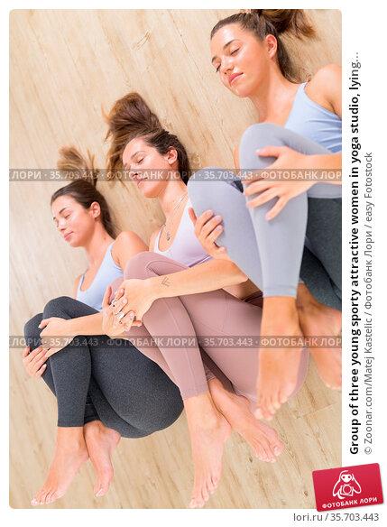 Group of three young sporty attractive women in yoga studio, lying... Стоковое фото, фотограф Zoonar.com/Matej Kastelic / easy Fotostock / Фотобанк Лори