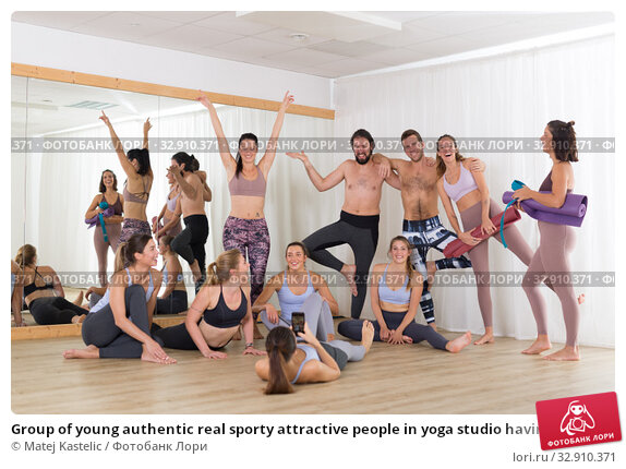 Group of young authentic real sporty attractive people in yoga studio having fun relaxing and socializing after hot yoga class. Healthy active lifestyle, working out in gym. Стоковое фото, фотограф Matej Kastelic / Фотобанк Лори