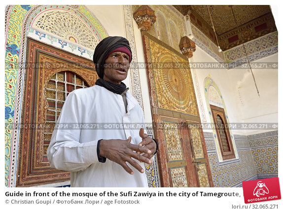 Guide in front of the mosque of the Sufi Zawiya in the city of Tamegroute, Draa River valley, Province of Zagora, Region Draa-Tafilalet, Morocco, North West Africa. (2019 год). Редакционное фото, фотограф Christian Goupi / age Fotostock / Фотобанк Лори