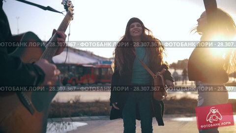 Купить «Guitar player in front of happy dancing girls at the street», видеоролик № 28307367, снято 11 декабря 2018 г. (c) Константин Шишкин / Фотобанк Лори