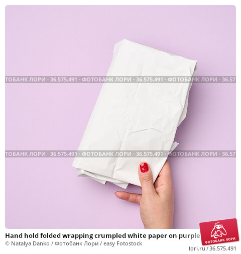Hand hold folded wrapping crumpled white paper on purple background. Стоковое фото, фотограф Natalya Danko / easy Fotostock / Фотобанк Лори