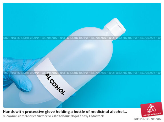 Hands with protective glove holding a bottle of medicinal alcohol... Стоковое фото, фотограф Zoonar.com/Andres Victorero / easy Fotostock / Фотобанк Лори
