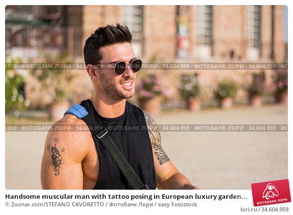 Handsome muscular man with tattoo posing in European luxury garden... Стоковое фото, фотограф Zoonar.com/STEFANO CAVORETTO / easy Fotostock / Фотобанк Лори