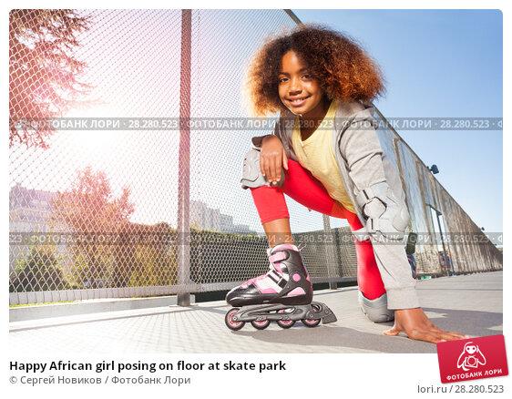 Купить «Happy African girl posing on floor at skate park», фото № 28280523, снято 14 октября 2017 г. (c) Сергей Новиков / Фотобанк Лори