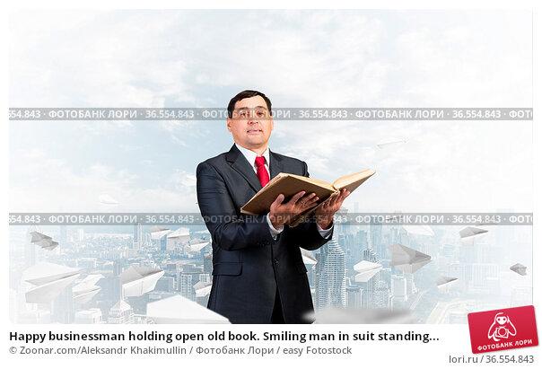 Happy businessman holding open old book. Smiling man in suit standing... Стоковое фото, фотограф Zoonar.com/Aleksandr Khakimullin / easy Fotostock / Фотобанк Лори
