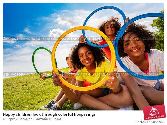 Happy children look through colorful hoops rings. Стоковое фото, фотограф Сергей Новиков / Фотобанк Лори