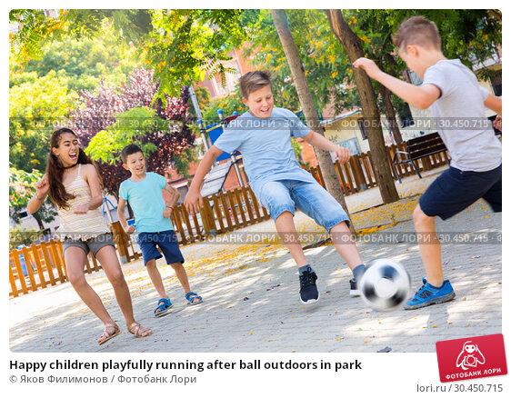 Happy children playfully running after ball outdoors in park. Стоковое фото, фотограф Яков Филимонов / Фотобанк Лори