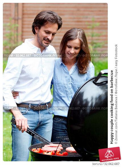 Happy couple cooking food on barbecue. Стоковое фото, фотограф Zoonar.com/Tatiana Badaeva / easy Fotostock / Фотобанк Лори