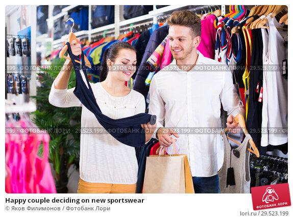 Купить «Happy couple deciding on new sportswear», фото № 29523199, снято 22 ноября 2016 г. (c) Яков Филимонов / Фотобанк Лори