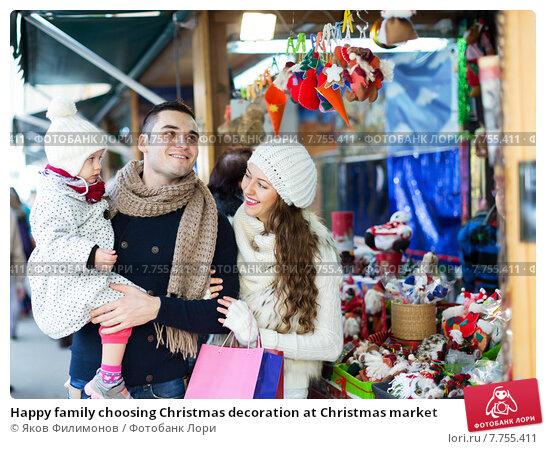 Купить «Happy family choosing Christmas decoration at Christmas market», фото № 7755411, снято 17 июля 2019 г. (c) Яков Филимонов / Фотобанк Лори