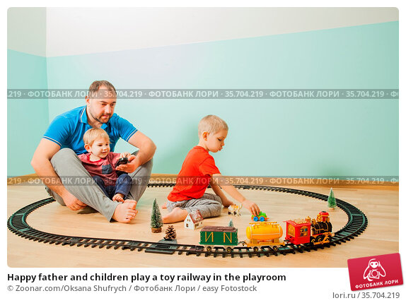Happy father and children play a toy railway in the playroom. Стоковое фото, фотограф Zoonar.com/Oksana Shufrych / easy Fotostock / Фотобанк Лори