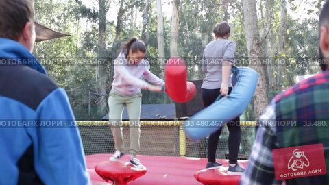 Купить «Happy female friends fighting by inflatable logs on adults bouncy playground outdoor», видеоролик № 33480467, снято 12 ноября 2019 г. (c) Яков Филимонов / Фотобанк Лори