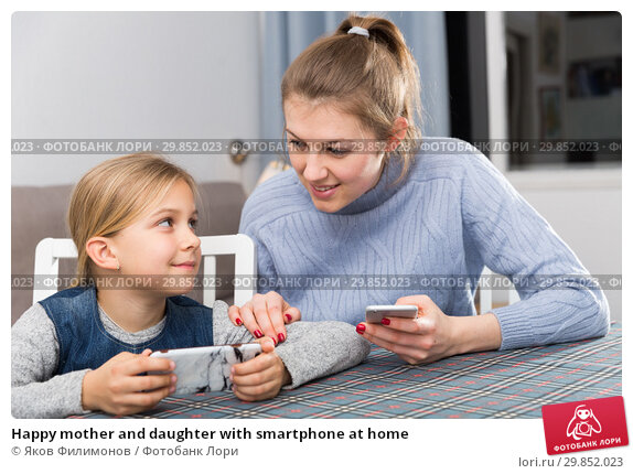 Купить «Happy mother and daughter with smartphone at home», фото № 29852023, снято 22 января 2019 г. (c) Яков Филимонов / Фотобанк Лори