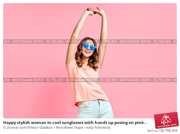 Happy stylish woman in cool sunglasses with hands up posing on pink... Стоковое фото, фотограф Zoonar.com/Viktor Gladkov / easy Fotostock / Фотобанк Лори