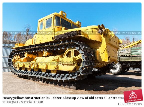 Купить «Heavy yellow construction bulldozer. Closeup view of old caterpillar tractor», фото № 26123375, снято 29 апреля 2017 г. (c) FotograFF / Фотобанк Лори