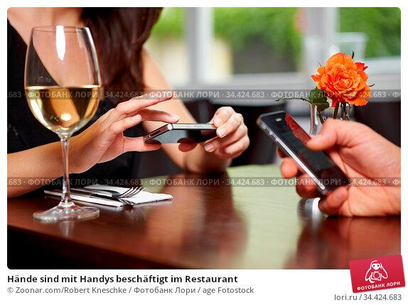 Hände sind mit Handys beschäftigt im Restaurant. Стоковое фото, фотограф Zoonar.com/Robert Kneschke / age Fotostock / Фотобанк Лори