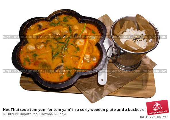 Купить «Hot Thai soup tom yum (or tom yam) in a curly wooden plate and a bucket of rice served on a board isolated on a white background», фото № 28307799, снято 14 апреля 2018 г. (c) Евгений Харитонов / Фотобанк Лори