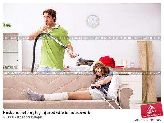 Husband helping leg injured wife in housework. Стоковое фото, фотограф Elnur / Фотобанк Лори