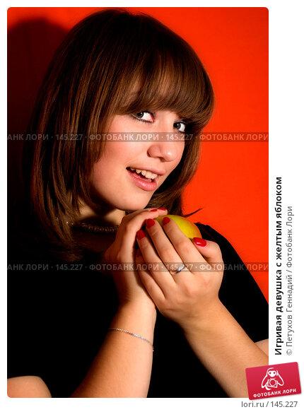 Игривая девушка с желтым яблоком, фото № 145227, снято 18 ноября 2007 г. (c) Петухов Геннадий / Фотобанк Лори