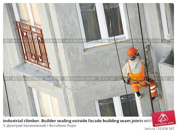 Купить «industrial climber. Builder sealing outside facade building seam joints with insulation mastic», фото № 33018167, снято 22 мая 2012 г. (c) Дмитрий Калиновский / Фотобанк Лори