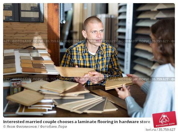 Interested married couple chooses a laminate flooring in hardware store. Стоковое фото, фотограф Яков Филимонов / Фотобанк Лори