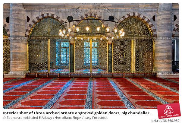 Interior shot of three arched ornate engraved golden doors, big chandelier... Стоковое фото, фотограф Zoonar.com/Khaled ElAdawy / easy Fotostock / Фотобанк Лори