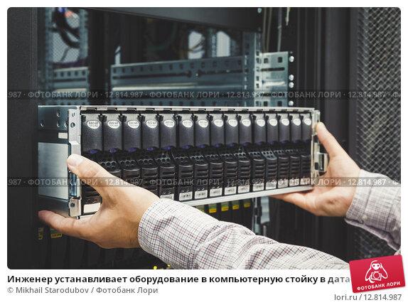 Купить «Инженер устанавливает оборудование в компьютерную стойку в дата-центре», фото № 12814987, снято 20 апреля 2019 г. (c) Mikhail Starodubov / Фотобанк Лори