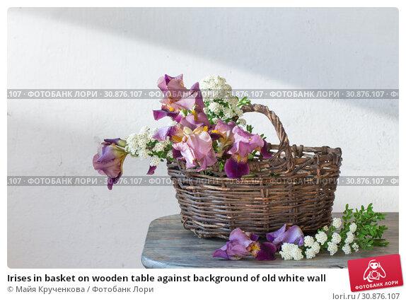 Купить «Irises in basket on wooden table against background of old white wall», фото № 30876107, снято 4 июня 2019 г. (c) Майя Крученкова / Фотобанк Лори