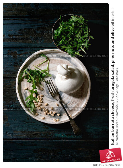 Купить «Italian burrata cheese, fresh arugula salad, pine nuts and olive oil in white ceramic plate with fork over dark wooden plank background. Flat lay, space», фото № 30987931, снято 19 июля 2019 г. (c) age Fotostock / Фотобанк Лори