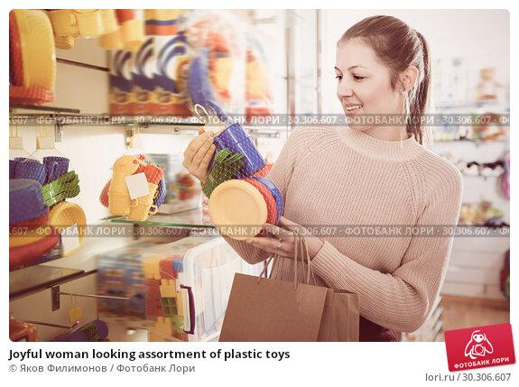 Купить «Joyful woman looking assortment of plastic toys», фото № 30306607, снято 19 декабря 2017 г. (c) Яков Филимонов / Фотобанк Лори