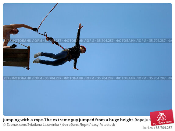 Jumping with a rope.The extreme guy jumped from a huge height.Ropejumping... Стоковое фото, фотограф Zoonar.com/Sviatlana Lazarenka / easy Fotostock / Фотобанк Лори