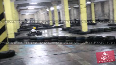 Купить «Kart racing. Kart racing in a closed parking area», видеоролик № 29511335, снято 11 декабря 2018 г. (c) Евгений Ткачёв / Фотобанк Лори