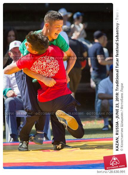 Купить «KAZAN, RUSSIA - JUNE 23, 2018: Traditional Tatar festival Sabantuy - Two male teenagers fighting in folk wrestling kuresh», фото № 28630991, снято 23 июня 2018 г. (c) Константин Шишкин / Фотобанк Лори