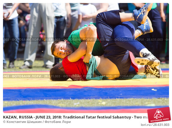 Купить «KAZAN, RUSSIA - JUNE 23, 2018: Traditional Tatar festival Sabantuy - Two male wrestlers fighting on tatami in folk kuresh battle», фото № 28631003, снято 23 июня 2018 г. (c) Константин Шишкин / Фотобанк Лори