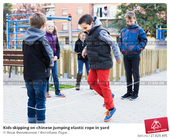 Купить «Kids skipping on chinese jumping elastic rope in yard», фото № 27829495, снято 15 мая 2018 г. (c) Яков Филимонов / Фотобанк Лори