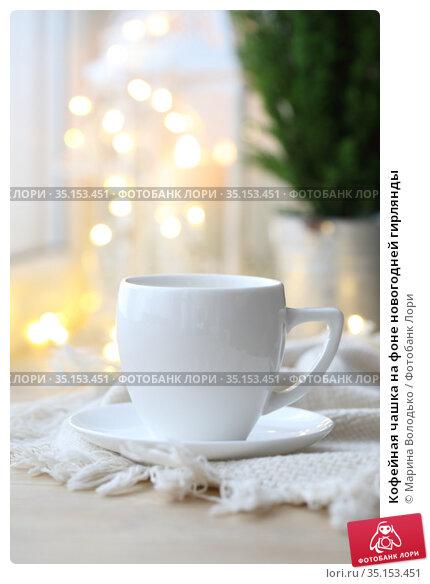Кофейная чашка на фоне новогодней гирлянды. Стоковое фото, фотограф Марина Володько / Фотобанк Лори
