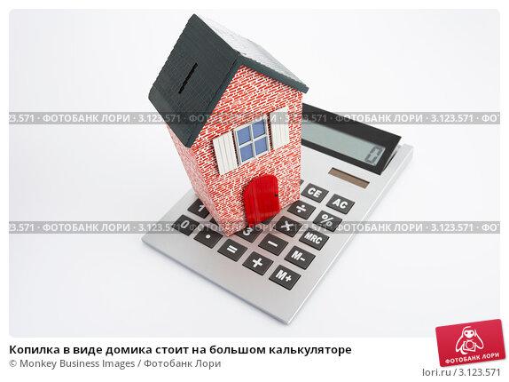 Купить «Копилка в виде домика стоит на большом калькуляторе», фото № 3123571, снято 20 июля 2011 г. (c) Monkey Business Images / Фотобанк Лори