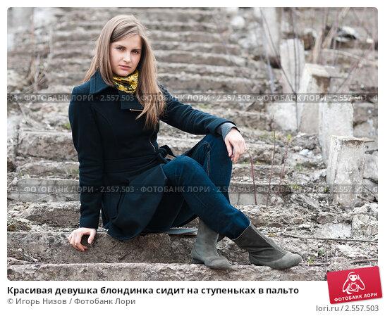 Девушка сидит на ступеньках в черном плаще смотрит в сторону